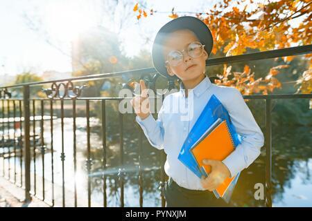 Little smart boy in glasses with books, shows index finger upwards idea, eureka. Background autumn sunny park, golden hour. - Stock Photo
