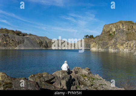 man at beautiful lake in an abandoned quarry with cliffs and boulders - Stock Photo
