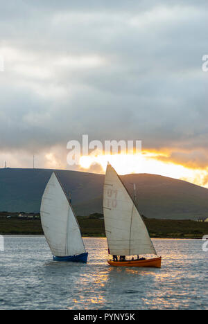 custom yawl sailboat race at sunset on Achill Island with beautiful golden light on a summer's evening - Stock Photo