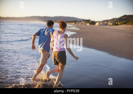 Young couple holding hands while running through water on a sandy beach. - Stock Photo