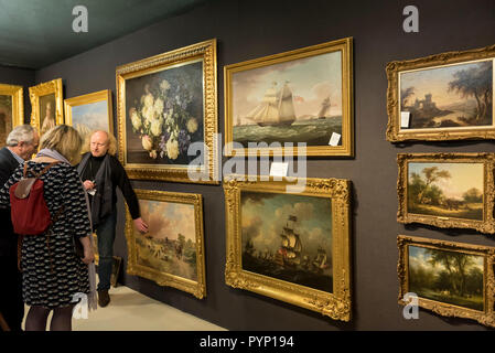 London, UK.  29 October 2018. A dealer shows 19th century paintings to visitors at the Winter Arts & Antiques Fair at Olympia.  70 of the UK's top dealers are selling everything from diamonds to dining tables and from clocks to ceramics.  The show runs until 4 November 2018.  Credit: Stephen Chung / Alamy Live News - Stock Photo