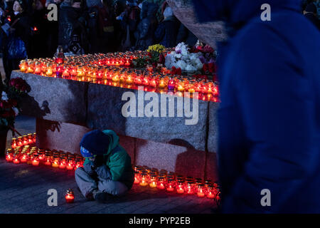 Moscow, Russia. 29th October, 2018 People lay flowers and light candles as they take part in an event commemorating the victims of political repression by the Solovetsky Stone monument in Lubyanka Square on the eve of Day of Remembrance of the Victims of Political Repression Credit: Nikolay Vinokurov/Alamy Live News - Stock Photo