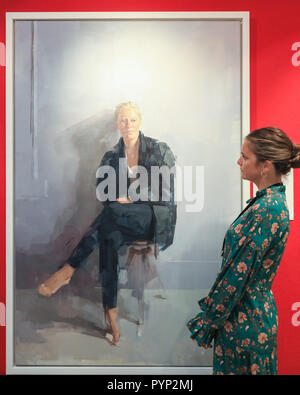 Olympia Exhibition Centre, London, UK, 29th Oct 2018. A gallery assistant from Fine Art Commissions looks at a commissioned portrait painting by Rosalie Watkins. The Winter Art and Antiques Fair at Olympia London will run Oct 30-Nov 4. Credit: Imageplotter News and Sports/Alamy Live News - Stock Photo