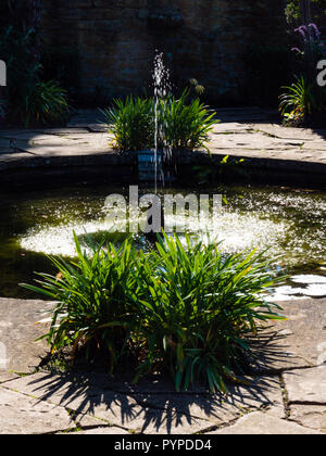 Fountain providing sound and movement in a small round pool at Tintinhull House and Garden in Somerset UK - Stock Photo
