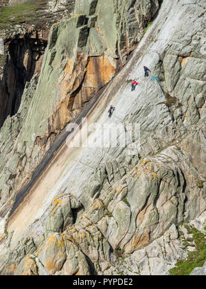 Climbers on the sheer face of The Devil's Slide the longest single granite slab climb in Europe - Lundy Island off Devon UK - Stock Photo