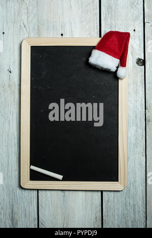 empty black chalkboard with white chalk on a white, rustic background, next to it lies the cap of Saint Nicholas - Stock Photo