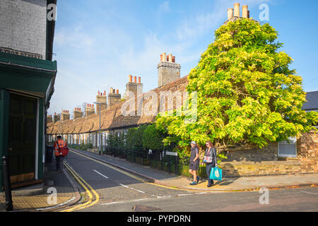 A row of terraced cottages with steep roofs and tall chimneys on Orchard street, near the town centre of Cambridge, England. - Stock Photo
