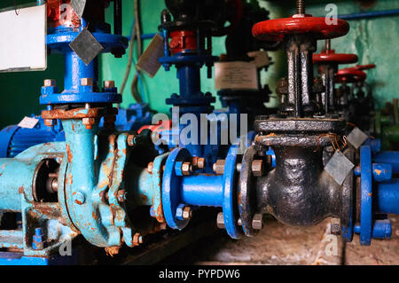 Several old black shutters with red handles on the cold water pipe colored in blue. - Stock Photo