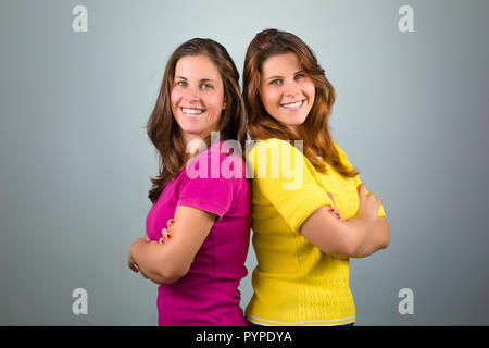 Twin Sisters on Gray Background - Stock Photo