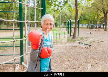 Portrait Of Fit Senior Woman With Boxing Glove At Outdoor Fitness Park In Sportswear. Active Old People Healthy Lifestyle - Stock Photo