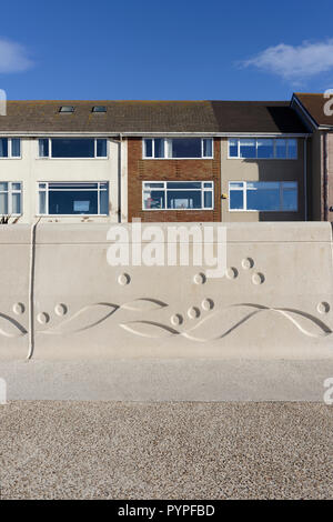 Pre cast concrete sea wall with Mythic Coast artwork, row of houses in background on Cleveleys promenade, part of coastal sea defences, fylde coast uk - Stock Photo