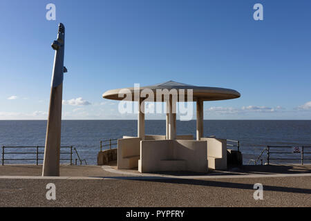 Pre cast concrete shelter with curved roof on Cleveleys promenade, sunny evening light with long shadows, calm sea in the background,  Fylde coast uk - Stock Photo