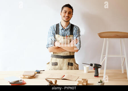 Confident young woodworker standing next to workbench in his carpentry workshop - Stock Photo