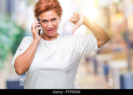 Atrractive senior caucasian redhead woman talking on smartphone over isolated background with angry face, negative sign showing dislike with thumbs do - Stock Photo