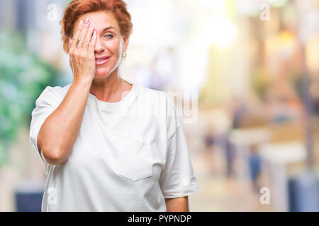 Atrractive senior caucasian redhead woman over isolated background covering one eye with hand with confident smile on face and surprise emotion. - Stock Photo