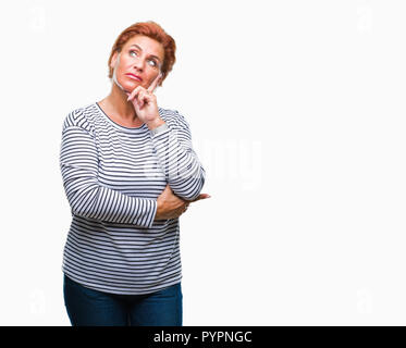 Atrractive senior caucasian redhead woman over isolated background with hand on chin thinking about question, pensive expression. Smiling with thought - Stock Photo