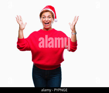Atrractive senior caucasian redhead woman wearing christmas hat over isolated background celebrating mad and crazy for success with arms raised and cl - Stock Photo