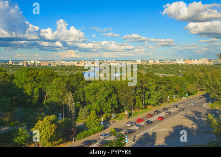 Sunny skyline of Kiev city on green banks of the Dnipro river with traffic on road, Ukraine - Stock Photo
