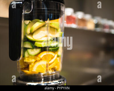 Blender with fresh fruits and vegetables for a green smoothie - Oranges, Apples, Cucumber - Stock Photo