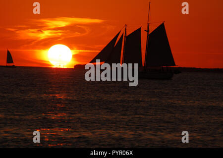 Boats drifting in front of the sunset in Key West, Florida - Stock Photo