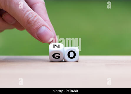Hand is turning dice and changes the word go to no - Stock Photo