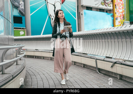 full length young lady traveler relaxing walking on the bridge with map. beautiful lady holding paper map searching the road to the next osaka sightse - Stock Photo
