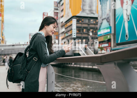 lady traveler using cellphone texting sms message. young backpacker relying next to the canal in osaka. beautiful tourist on mobile phone chatting bes - Stock Photo