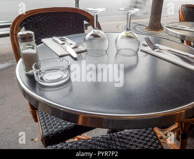 View of Glassware and Silverware in small round Table on Outdoor Cafe - Stock Photo