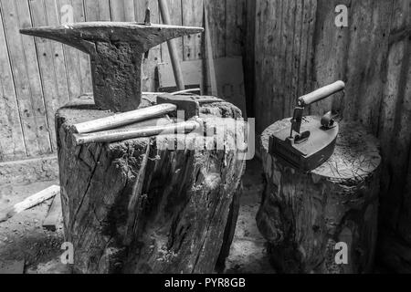 Antique anvil and hammers in a workshop in old Swedish farm in northern Sweden - Stock Photo