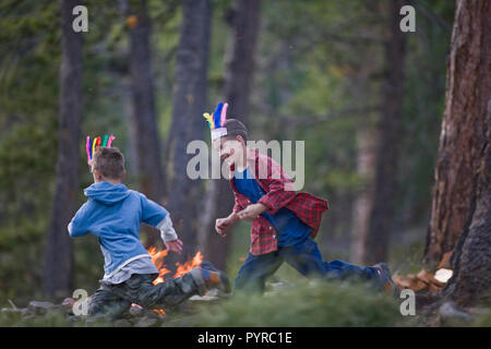 Two young brothers wearing feathered hats while chasing each other in a forest. - Stock Photo
