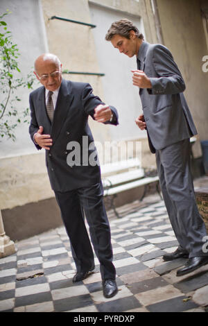 Senior business man teaching a mid-adult male colleague to dance in a courtyard. - Stock Photo