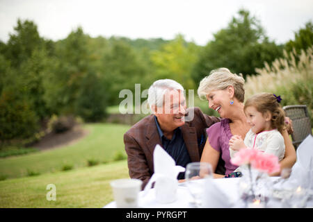 Happy young girl sitting with her mature grandmother and grandfather outside. - Stock Photo