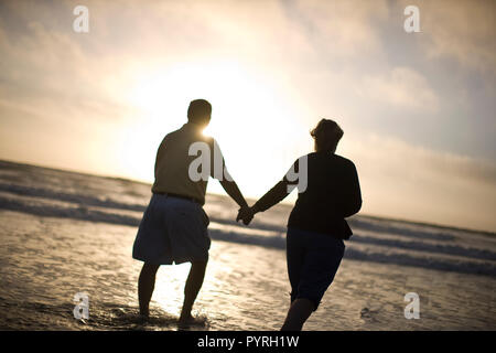 Couple holding hands while walking along a beach at sunset. - Stock Photo