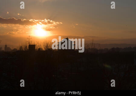 Sun setting over a city scape. - Stock Photo