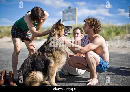 Three young men patting a dog. - Stock Photo
