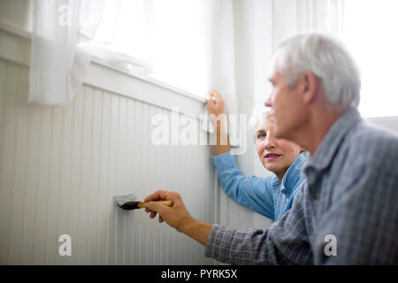 Happy senior couple painting the inside of their house. - Stock Photo