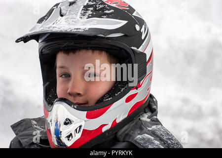 Portrait of a boy wearing a crash helmet in the snow. - Stock Photo