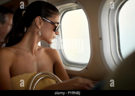 Content young woman looking out an airplane window. - Stock Photo