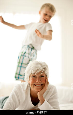 Mature woman smiles and rests her head on her hand as she lies owith her young grandson standing on the bed behind her as they pose for a portrait. - Stock Photo