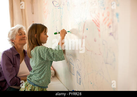 Mature woman happily watches her young granddaughter write on a bedroom mural wall with a felt pen. - Stock Photo