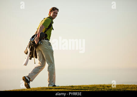 Portrait of a smiling mid adult man walking on a gold course. - Stock Photo