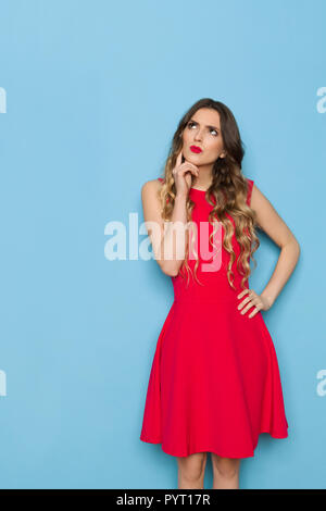 Beautiful young woman in red mini dress is holding hand on chin, looking up and thinking. Three quarter length studio shot on blue background. - Stock Photo
