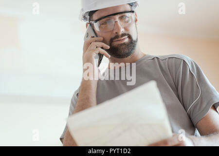 Smiling architect with safety helmet, he is checking a house project and having a phone call - Stock Photo