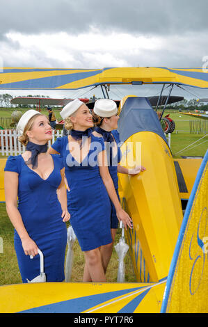 Females in retro airline stewardess style period dress looking up at planes in the sky with one of the airplanes on display at the Goodwood Revival - Stock Photo