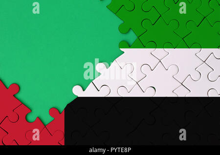 United Arab Emirates flag  is depicted on a completed jigsaw puzzle with free green copy space on the left side. - Stock Photo