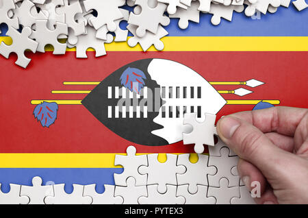 Swaziland flag  is depicted on a table on which the human hand folds a puzzle of white color. - Stock Photo