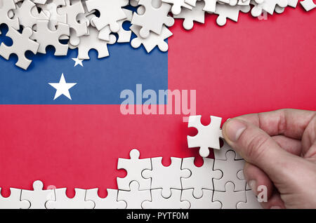 Samoa flag  is depicted on a table on which the human hand folds a puzzle of white color. - Stock Photo