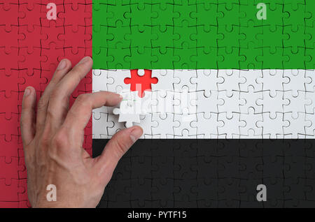 United Arab Emirates flag  is depicted on a puzzle, which the man's hand completes to fold. - Stock Photo