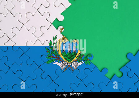 San Marino flag  is depicted on a completed jigsaw puzzle with free green copy space on the right side. - Stock Photo