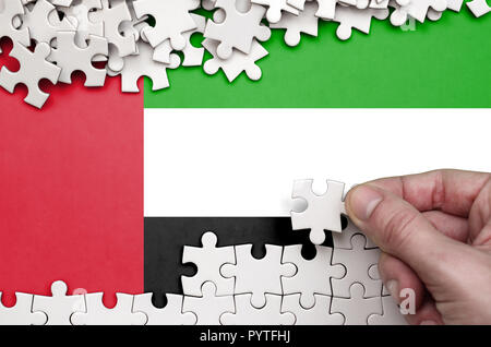 United Arab Emirates flag  is depicted on a table on which the human hand folds a puzzle of white color. - Stock Photo